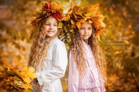Фото Две улыбающиеся девочки, с букетом из желтых листьев и в венках из листьев и рябины, стоят на осеннем фоне, фотограф Мусская Татьяна / Musskaya Tatiana