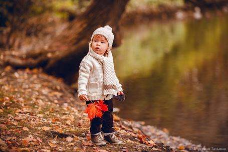 Фото Маленький ребенок, стоит у воды с красным кленовым листочком в одной руке, и игрушечной машинкой, в другой, фотограф Мусская Татьяна / Musskaya Tatiana