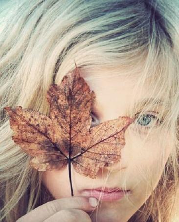 Фото Девушка прикрыла глаз осенним листом