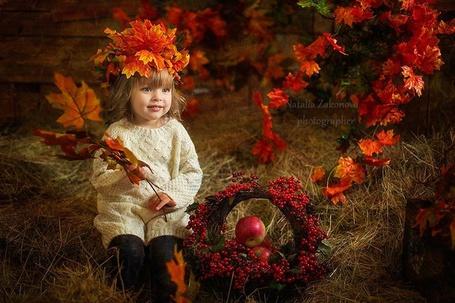 Фото Маленькая девочка сидит на стоге сена, на голове у нее украшение из осенних листьев, рядом висят ветки с багряными листьями, около девочки корзиночка, украшенная красными ягодами, в корзинке лежат яблоки