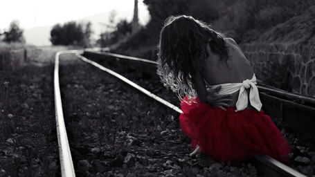 Фото Девушка в красной юбке, сидящая на рельсах