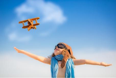 Фото Девочка смотрит на самолетик в небе