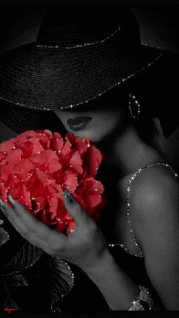 Фото Девушка в черной шляпке, с украшением на руке, держит букет цветов