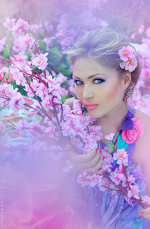 Фото Девушка с голубыми глазами, с розовыми цветами в волосах, держит в руках ветки с розовыми цветами
