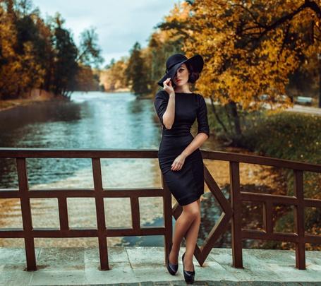 Фото Стильная девушка на мостике у водоема в осеннем парке