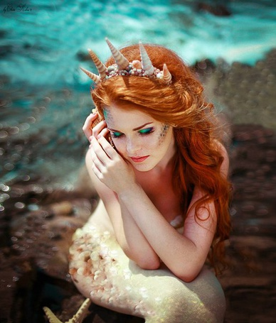 Фото Русалочка / The Little Mermaid из одноименной сказки прижимает к уху раковину, сидя на берегу