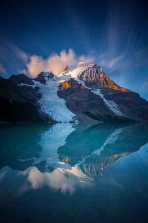 Фото Заснеженная гора около озера на фоне облачного неба, by Callum Snape