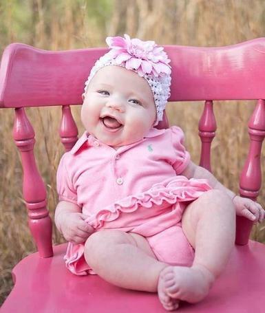 Фото Милая маленькая девочка сидит на стуле и улыбается