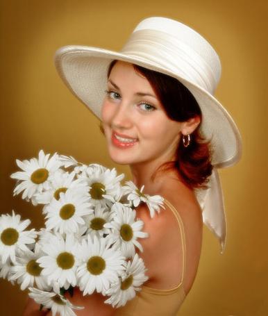 Фото Девушка в белой шляпе и с букетом ромашек. с очаровательной улыбкой