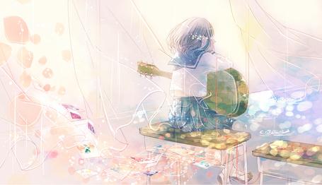 Фото Девушка с гитарой сидит на парте