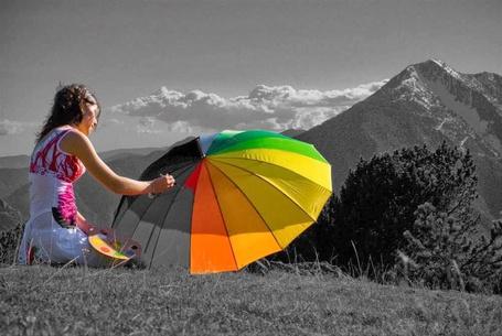 Фото Девушка сидит на траве, держит в руке палитру и разрисовывает кисточкой зонтик, на фоне неба и гор