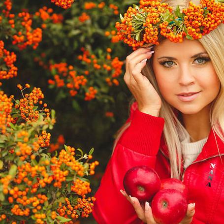 Фото Девушка блондинка в венке на голове из калины, стоит возле кустов с плодами калины, подняв одну руку к голове и держит в другой руке три красных яблока