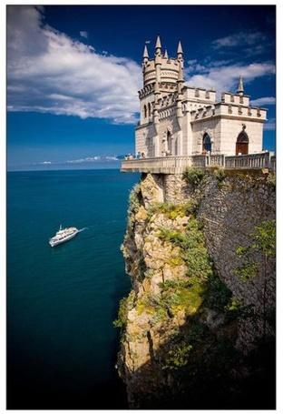 Фото Замок Ласточкино Гнездо, расположен на скале над морем, в городе Ялта. Внизу по морю плывет белый теплоход