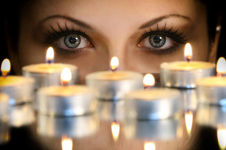 Фото Глаза девушки за маленькими горящими свечами, фотограф Александр Михеев