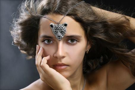Фото Темноволосая девушка приложила ко лбу цепочку с кулоном в виде морды леопарда