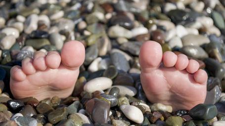 Фото Детские голенькие пяточки с пальчиками выглядывают из морской разноцветной гальки