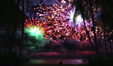 Фото Влюбленная пара, сидя на берегу ночного моря, наблюдают разноцветный фейерверк на ночном небе