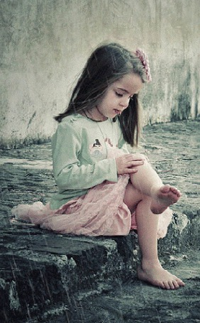 Фото Девочка сидит на тротуаре под дождем