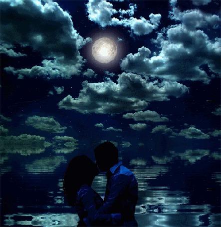 Фото Мужчина и девушка целуются на фоне неба с облаками, в котором кроется яркая полная луна
