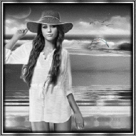 Фото Девушка в шляпе стоит на фоне моря, в небе летят чайки