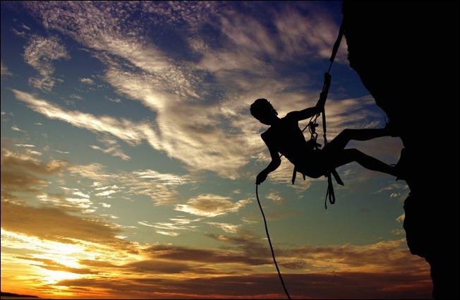 Фото Альпинист на скале на фоне облачного неба