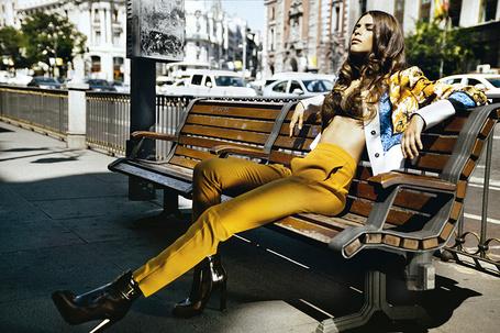 Фото Девушка в стильном наряде сидит на лавочке, прикрыв глаза