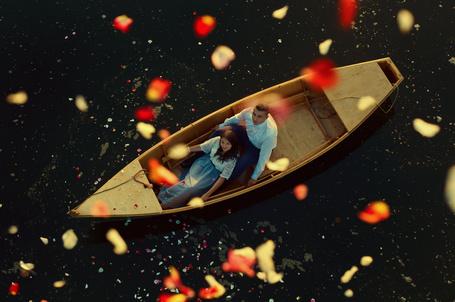 Фото Девушка и парень плывут в лодке, а сверху на них падают лепестки роз