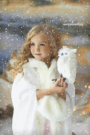 Фото Девочка с белой совой стоит под падающим снегом