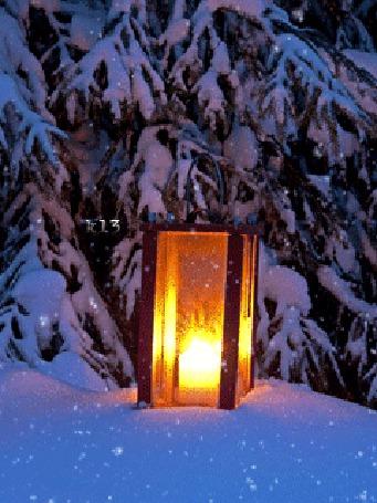 Фото Горящий фонарь стоит в снегу рядом с елями, идет снег