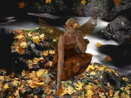 Фото Осень, падают листья, девушка с крыльями за спиной и венком из цветов на голове сидит на камнях, покрытых желтыми листьями, у воды