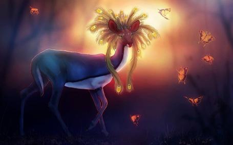 Фото Фантастическая лань с гривой в виде перьев павлина стоит на фоне сияния и в окружении летающих бабочек