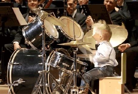 Фото Маленький ударник с большим удовольствием исполняет соло на барабанах в большом симфоническом оркестре