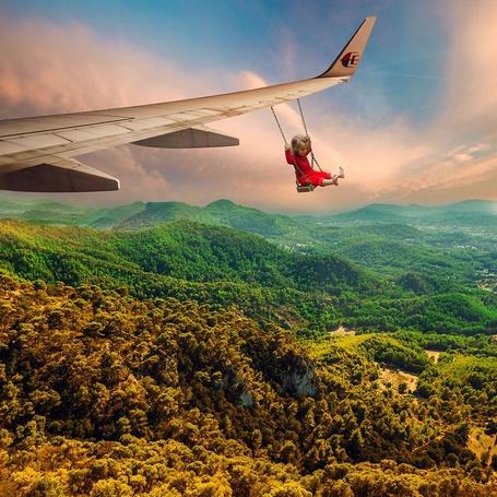 Фото Девочка на качели, которая весит на крыле самолета, ву Caras Ionut