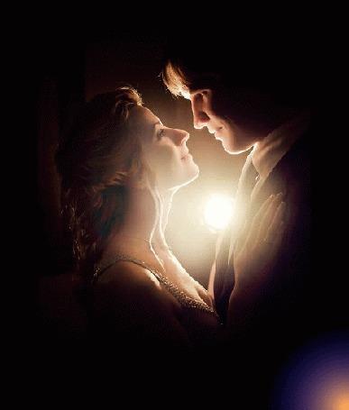 Фото Парень и девушка на темном фоне стоят и смотрят влюбленно друг другу в глаза, между ними взлетает и рассыпается в небе разноцветный фейерверк, автор Akela