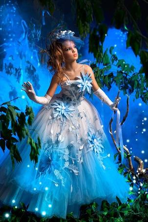 Фото Девушка в голубом наряде принцессы в сказочном лесу с голубым светом и летающими светлячками