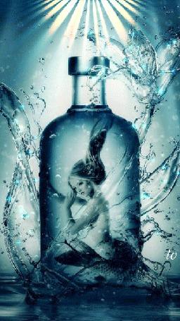 Фото Русалочки сидит в бутылке освященная лучами солнца проходящего сквозь воду