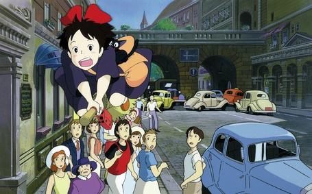 Фото Кики / Kiki и Джи-Джи / Jiji из аниме Kikis delivery service / Ведьмина служба доставки, летит с котом на метле по улице над группой удивленных людей