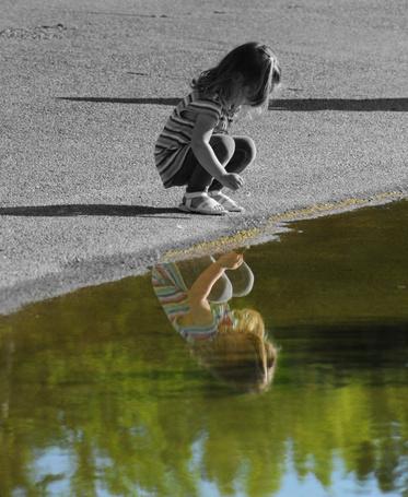 Фото Девочка смотрит на свое отражение в воде