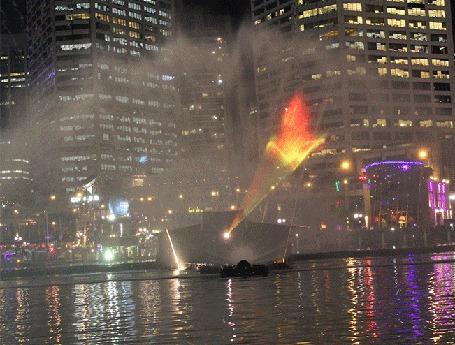 Фото Лазерная голограмма над водой в виде возникающей и пропадающей горящей птицы Феникс