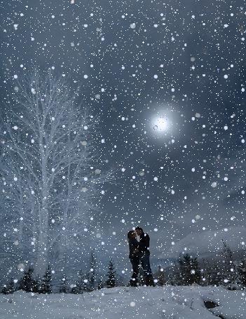 Фото Влюбленная пара стоит под падающим снегом