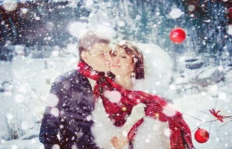 Фото Невеста в белом свадебном платье держит за красный шарф жениха на фоне снегопада и висящих на дереве елочных украшений в виде шаров