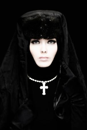 Фото Девушка монашка с голубыми глазами в черной зимней одежде с серебрянным крестом на серебрянной цепочке на шее
