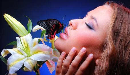 Фото Девушка закрыв глаза, подняла голову вверх, на нижней губе сидит разноцветная бабочка. рядом цветы белой лилии