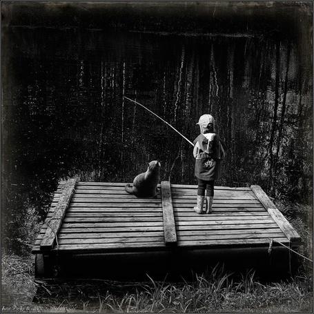 Фото Ребенок и кот рыбачат на мостках