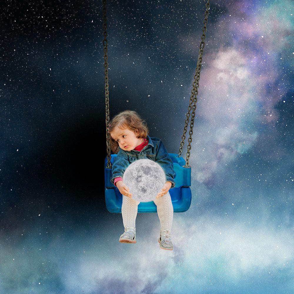 Фото Девочка на качелях в космосе держит в руках планету