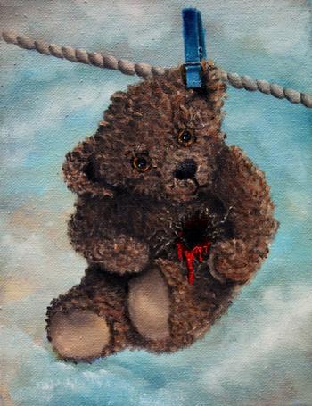 Фото Плюшевый мишка с вырванным сердцем висит на веревке