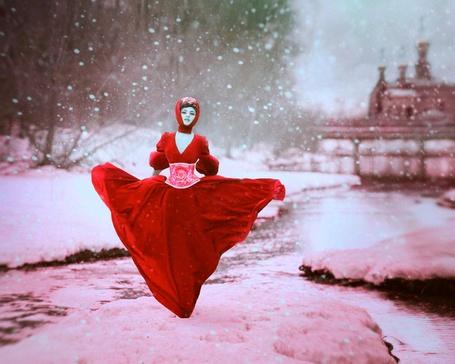 Фото Девушка в длинном красном платье и красном платке на голове стоит на снегу, с неба идет снег