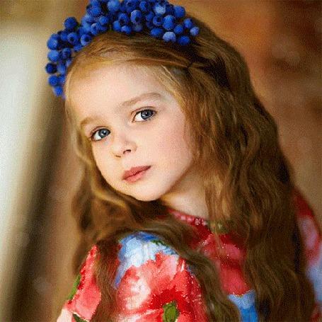Фото Девочка с распущенными волосами и веночком из синих ягод на голове открывает и закрывает свои прекрасные синие глаза