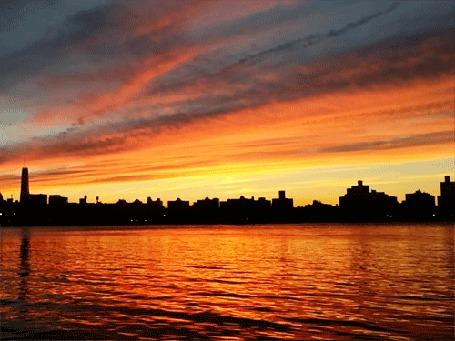 Фото Силуэты домов города на фоне закатного неба и морского берега
