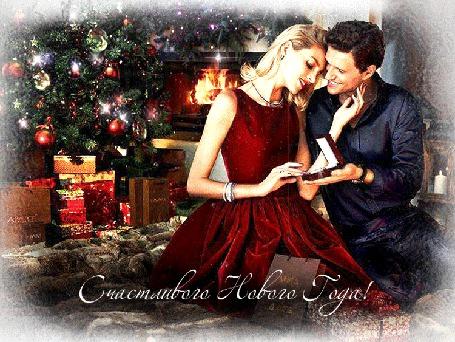 Фото Мужчина и женщина, в красивом, красном платье сидят на диване, мужчина дарит ей кольцо, обстановка новогоднего праздника, горит камин, наряжена новогодняя елка, в коробках лежат подарки. Счастливого Нового Года!
